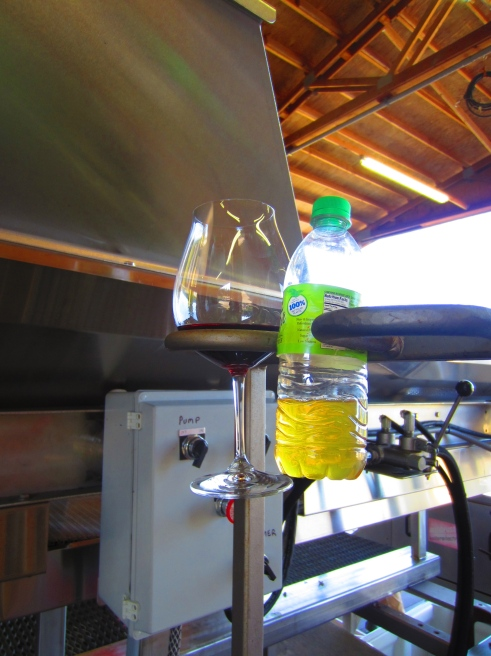 Since Dean designs, engineers and builds winery processing equipment—including the machines at use in his own facility, ADEA—he can make his own customizations. That includes some very handy wineglass and bottle holders on the side of the sorting table.