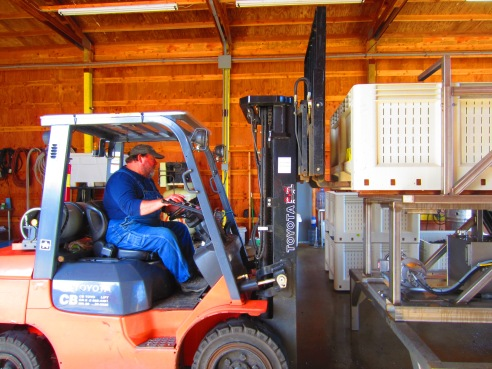 Dean Fisher of ADEA Wine Company loads the a bin of grapes into the hopper at the head of the sorting line.